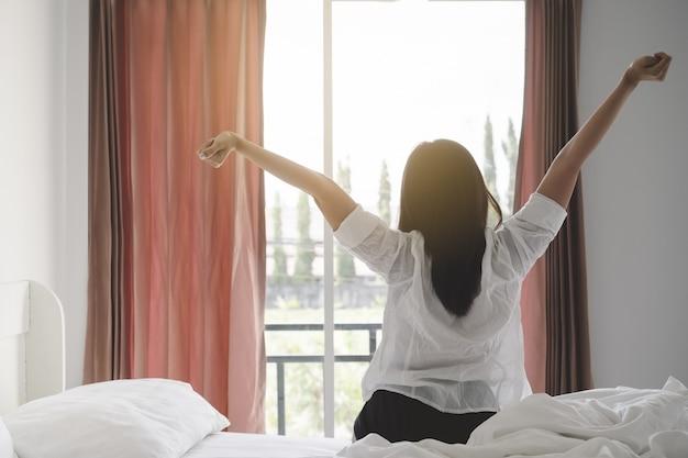 寝室で朝起きた後にベッドに伸びている幸せなアジアの女性。