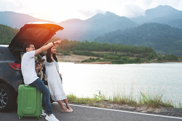 幸せで若いアジア人のカップルは、ペットと人生旅行を楽しんでいます。