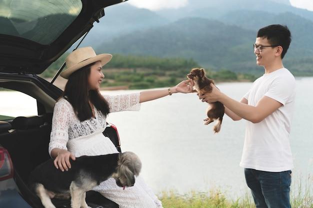 幸せで若いアジア人のカップルは、ペットと一緒に旅行ライフスタイルを楽しんでいます。