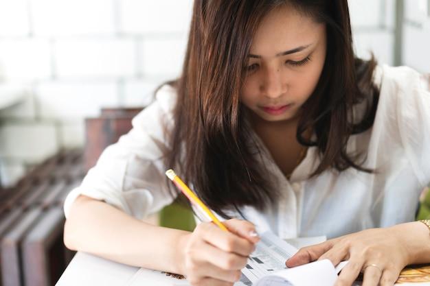 魅力的な若いアジアの女性は、鉛筆を使ってカフェの紙に書く。