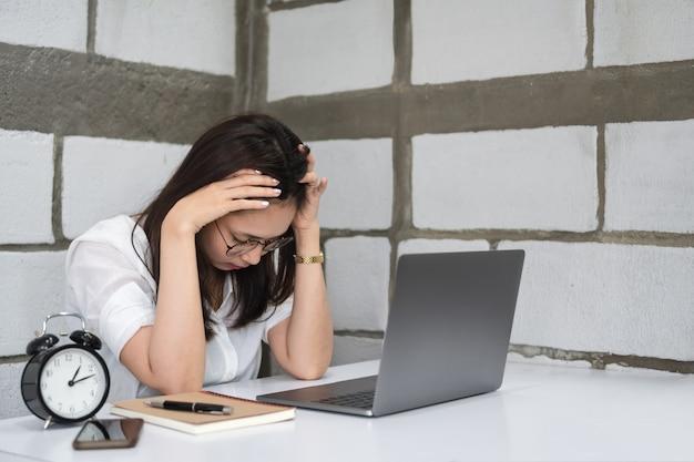 Утомленная молодая азиатская женщина в стеклах работая с компьтер-книжкой в офисе.