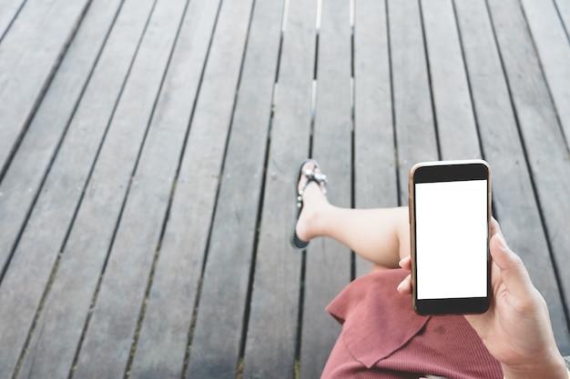 空白の白いデスクトップ画面で黒いスマートフォンを持っている女性の手のモックアップ画像。
