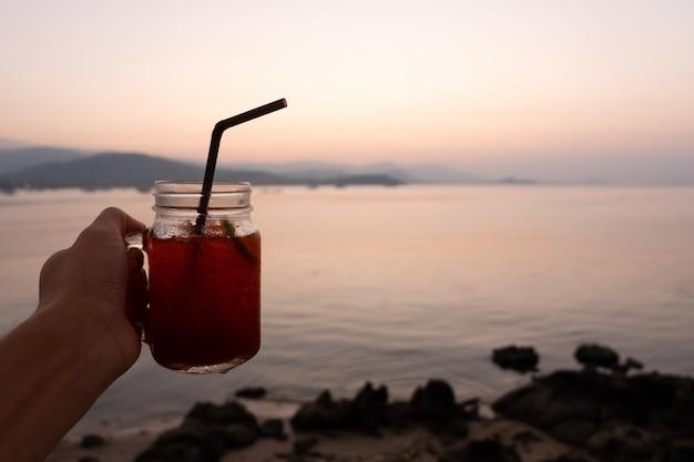 日没の熱帯海のビーチでレモン氷のガラスの手のひらを手に。