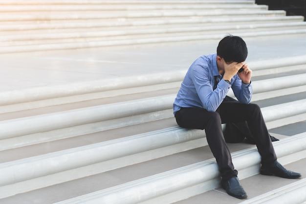 電話で話す階段に座っている若いアジア人のビジネスマンは強調しています。
