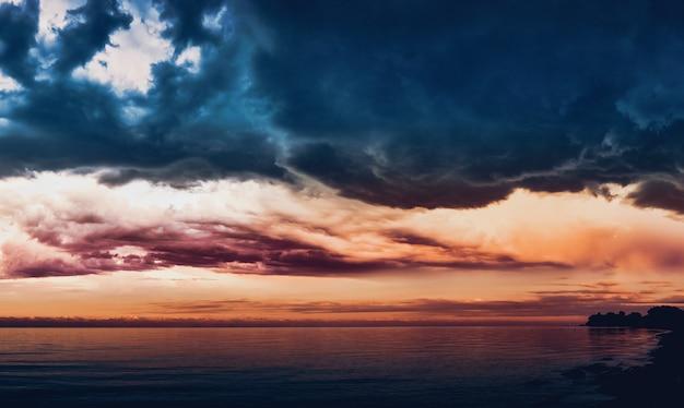 山の夜明け、夕暮れ時のエキサイティングで活気に満ちた荒れ模様の空を背景に、雲の切れ間から劇的な光。
