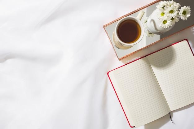 テキストのためのスペースを持つ赤いノートブック、お茶のマグカップ、ミラー付き真鍮製のトレイに白い花の花瓶とボイルファブリックの背景の朝のシーンのトップビュー