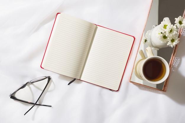 テキストのためのスペースと、赤いノートブック、メガネ、マグカップ、ミラー付き真鍮製のトレイに白い花の花瓶とボイルファブリックの背景の朝のシーンのトップビュー