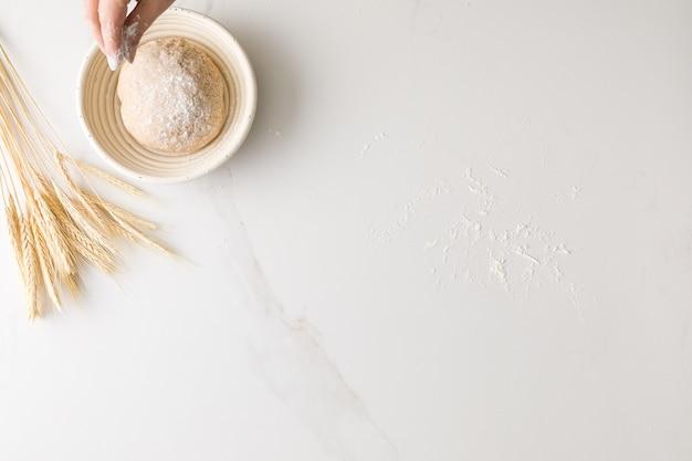 小麦と大理石のパン生地に小麦粉とテキスト用のスペースと小麦粉を注ぐ女性の手の上から見る