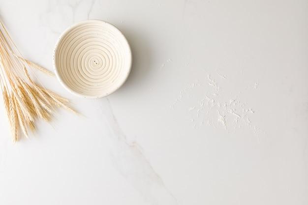空のパンボウル、小麦、小麦粉のテキスト用のスペースと大理石のテーブルのトップビュー