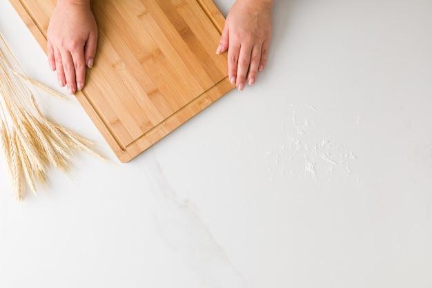 小麦と大理石のテーブルで木の板とテキスト用のスペースと小麦粉で休んでいる女性の手の上から見る