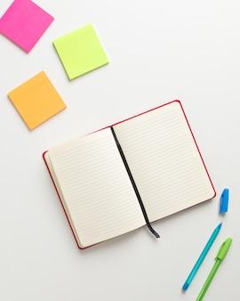 中央に開いている空白の赤いノート、上隅に色付きのリマインダー、下隅に青と緑のペンの平面図