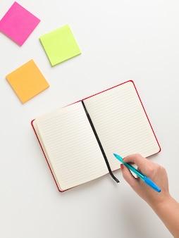 中央に開いている空白の赤いノート、ハイコーナーに色付きのリマインダー、青いペンを持つ女性の手の平面図
