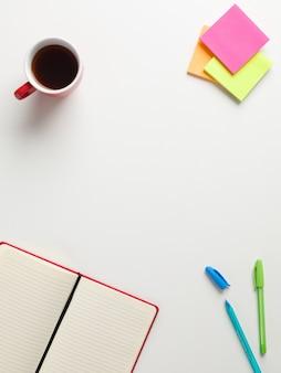 開いている赤いノート、色のリマインダー、青と緑のペンの平面図