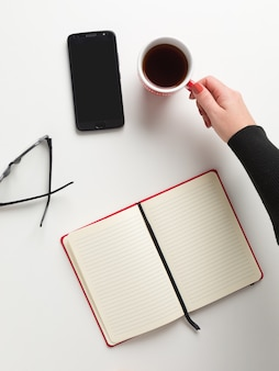 開いている赤いノート、コーヒーの赤いカップを持っている女性の手の上から見る