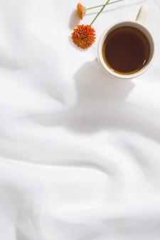 Взгляд сверху предпосылки ткани вуали с кружкой чая, оранжевого цветка и космоса для текста
