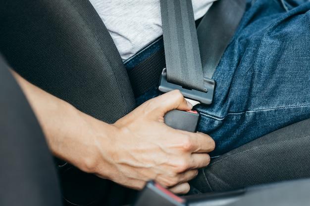 Мужская рука крепится ремнем безопасности автомобиля