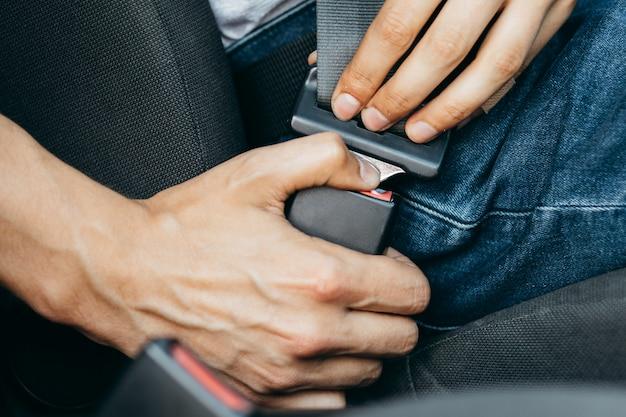 Мужские руки крепятся ремнем безопасности автомобиля