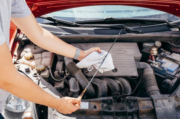 Человек, проверка моторного масла в автомобиле