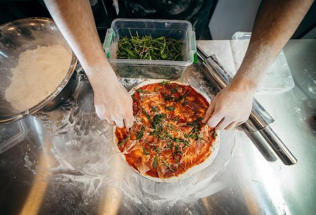 Сырое тесто для приготовления пиццы с ингредиентом: томатный соус, моцарелла, сыр, прошутто
