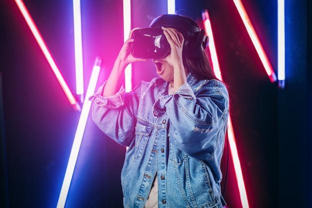 仮想現実の眼鏡を使用して青いデニムジャケットを持つ若い女性