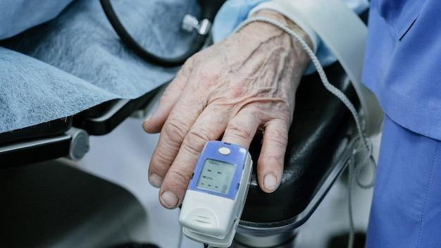 病院での手術中に監視するための指にパルスオキシメータを備えた老人患者