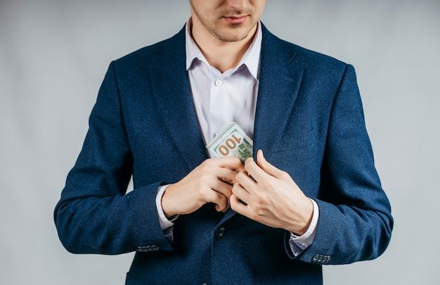 Бизнесмен кладет деньги в карман