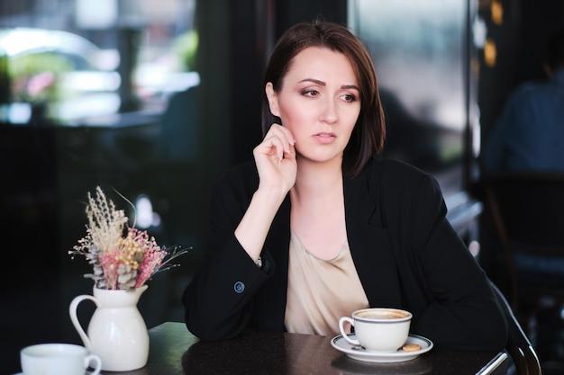 Красивая женщина, сидя за столом в кафе