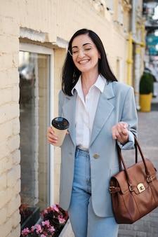 Стильная деловая женщина держит чашку кофе