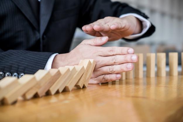 Рука бизнесмена останавливая падая деревянный эффект домино