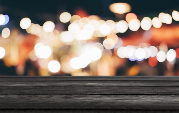 光スポットと抽象的なぼやけたお祭りの明るい背景の前に空の木製テーブル