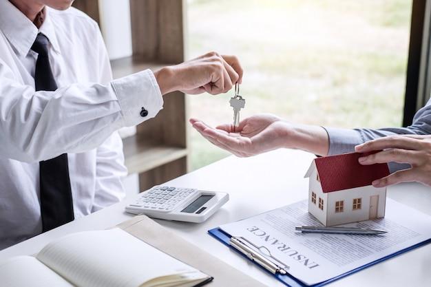 Менеджер по продажам недвижимости дает ключи клиенту после подписания договора аренды