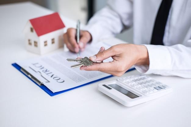 Агент по недвижимости менеджер по продажам держит ключи клиента после подписания договора аренды