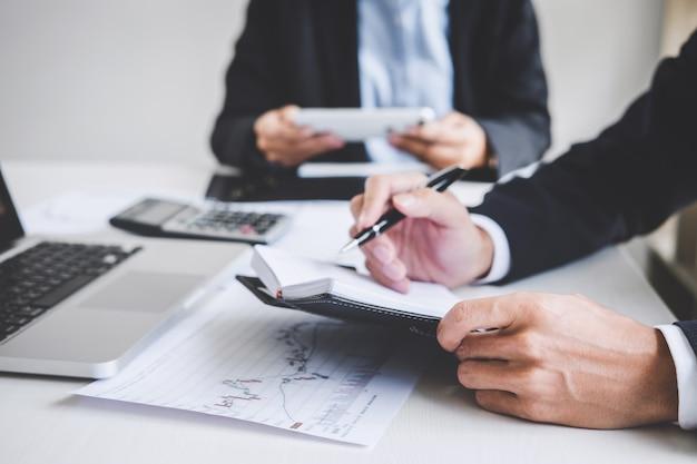 Бизнес команда двух коллег, работающих и анализ графика торговли на фондовом рынке
