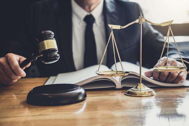 弁護士や裁判官の契約書、法律書、テーブルの上の木製の小槌での作業