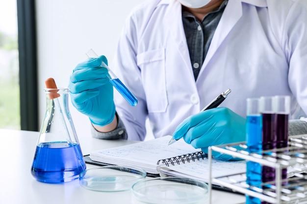 カラー液体の滴と試薬で試験管を保持している白衣の科学者または医療