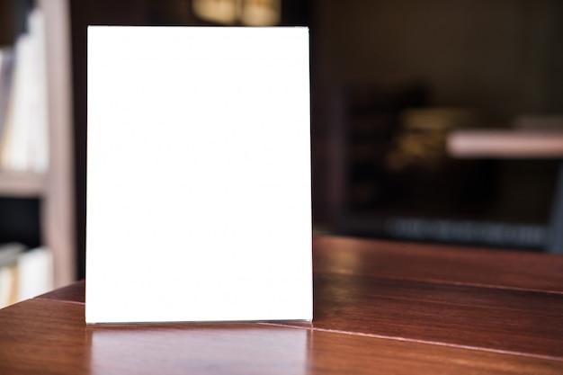 コーヒーショップのテーブルの上の空白のメニューフレームをモックアップあなたのテキストのために立つ
