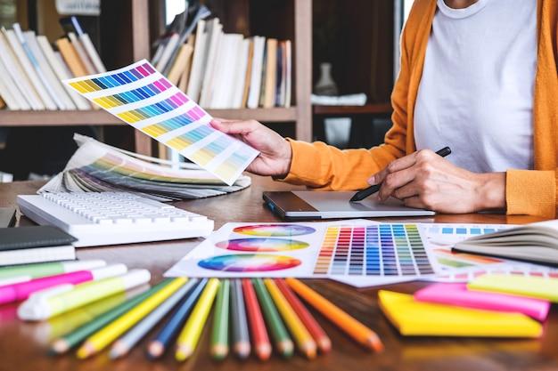 Изображение графического дизайнера, работающего над выбором цвета и нанесением на графический планшет