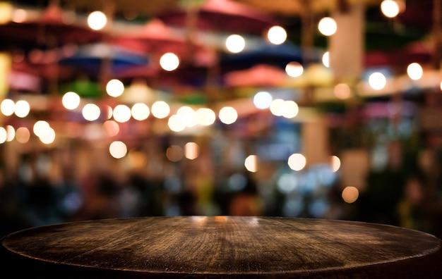 光スポットとボケ味を持つ抽象ぼやけお祝い光背景の前に空の木製テーブル
