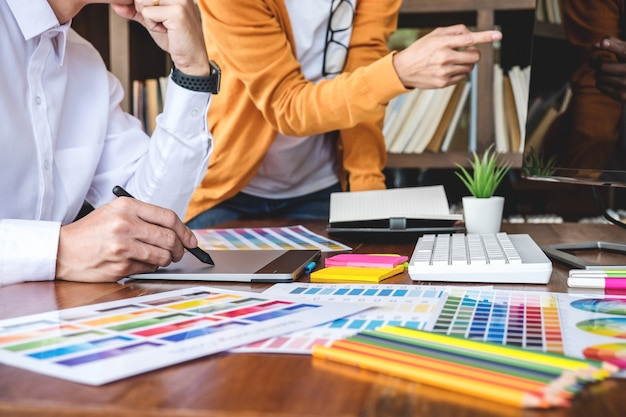Два графических дизайнера работают над подбором цвета и нанесением на графический планшет
