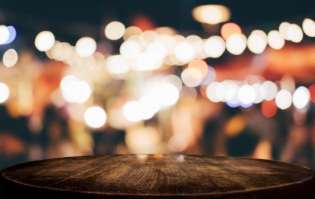 光スポットとボケ味を持つ抽象的なぼやけたお祭りの明るい背景の前に空の木製テーブル