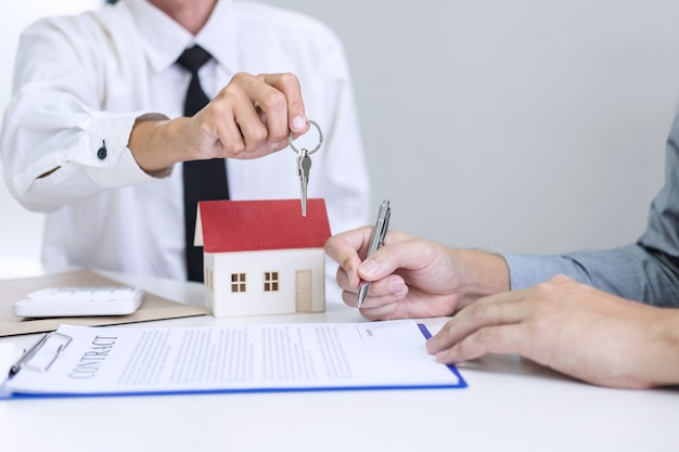 Менеджер по продажам дает ключи клиенту после подписания договора аренды, договора купли-продажи