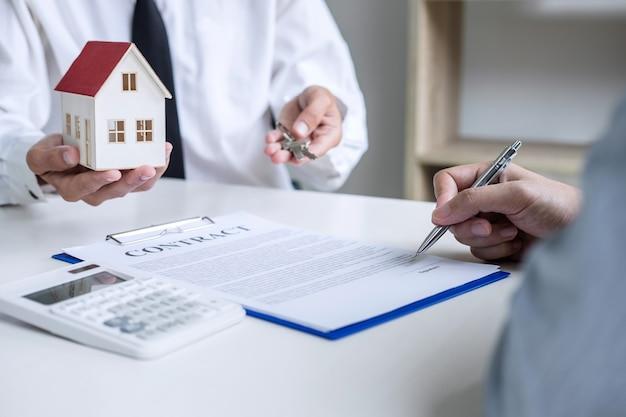 Менеджер по продажам держит ключи у клиента после подписания договора аренды