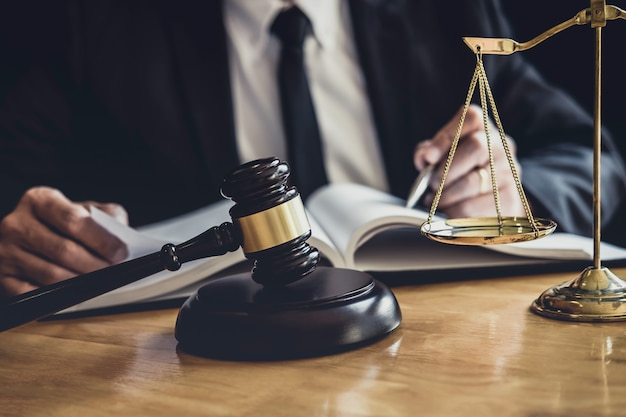 弁護士や裁判官の契約書、法律書、法廷のテーブルの上の木製の小槌での作業