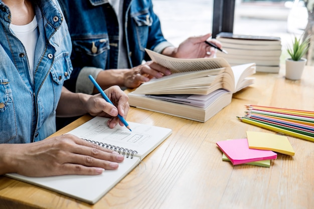 Два старшеклассника или одноклассники вместе помогают другу делать домашние задания в классе