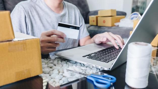 若い男がオンラインショッピングの小包を開くボックスとクレジットカードで商品を購入する