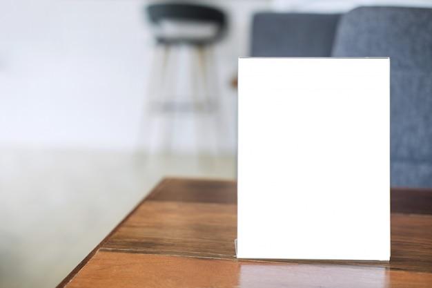 コーヒーショップのテーブルの上の空白のメニューフレームは、あなたのテキストを表す