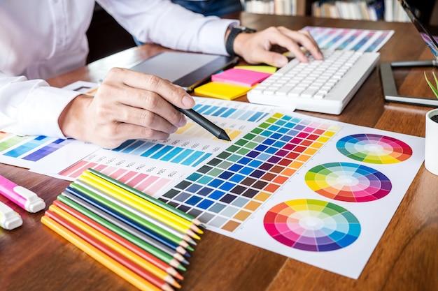 Креативный графический дизайнер, работающий над выбором цвета и нанесением на графический планшет на рабочем месте