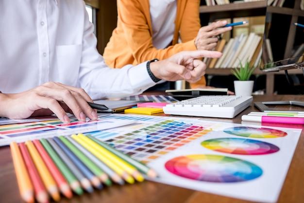 Два креативных графических дизайнера работают над подбором цветов и нанесением на графический планшет