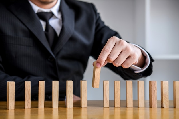 ドミノのラインに木製のブロックを配置するギャンブルの実業家の手のクローズアップ