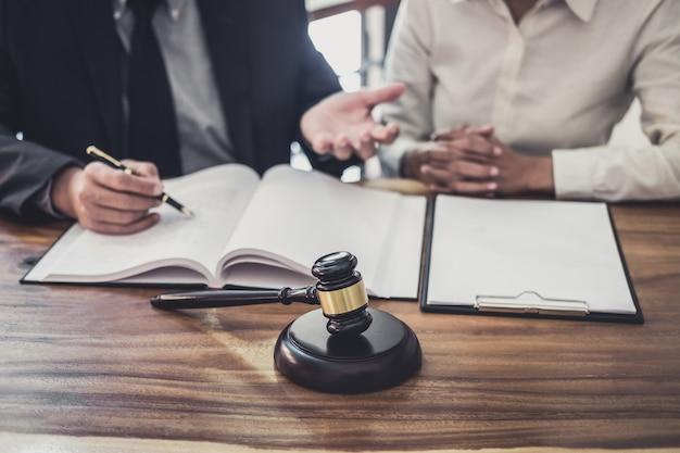 男性の弁護士または裁判官が、ビジネスウーマンクライアント、法律および司法サービスとのチーム会議を開催します。